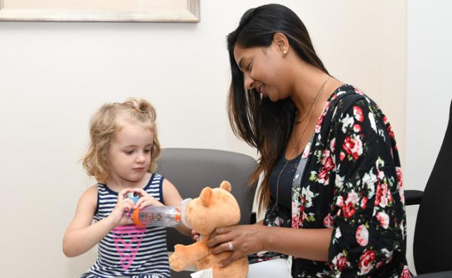 MSH respiratory therapist Shivani Jadav uses a special teddy bear to help asthma patient Payton Walker learn to administer her asthma medication.